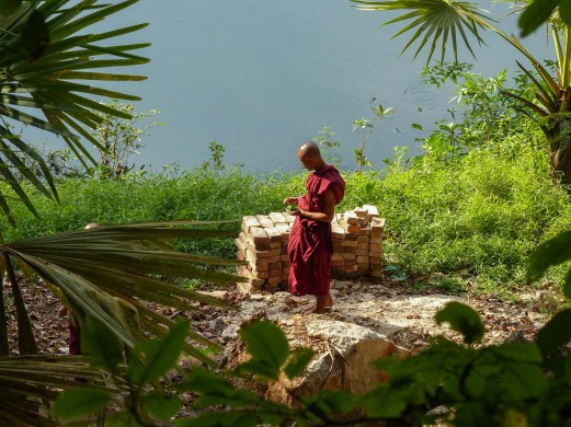 Monk in front of lake