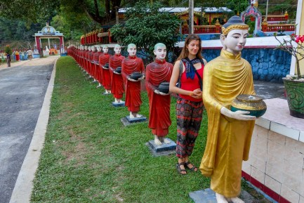 Maria in line with standing monk statues in front of Kawtka Taung Cave