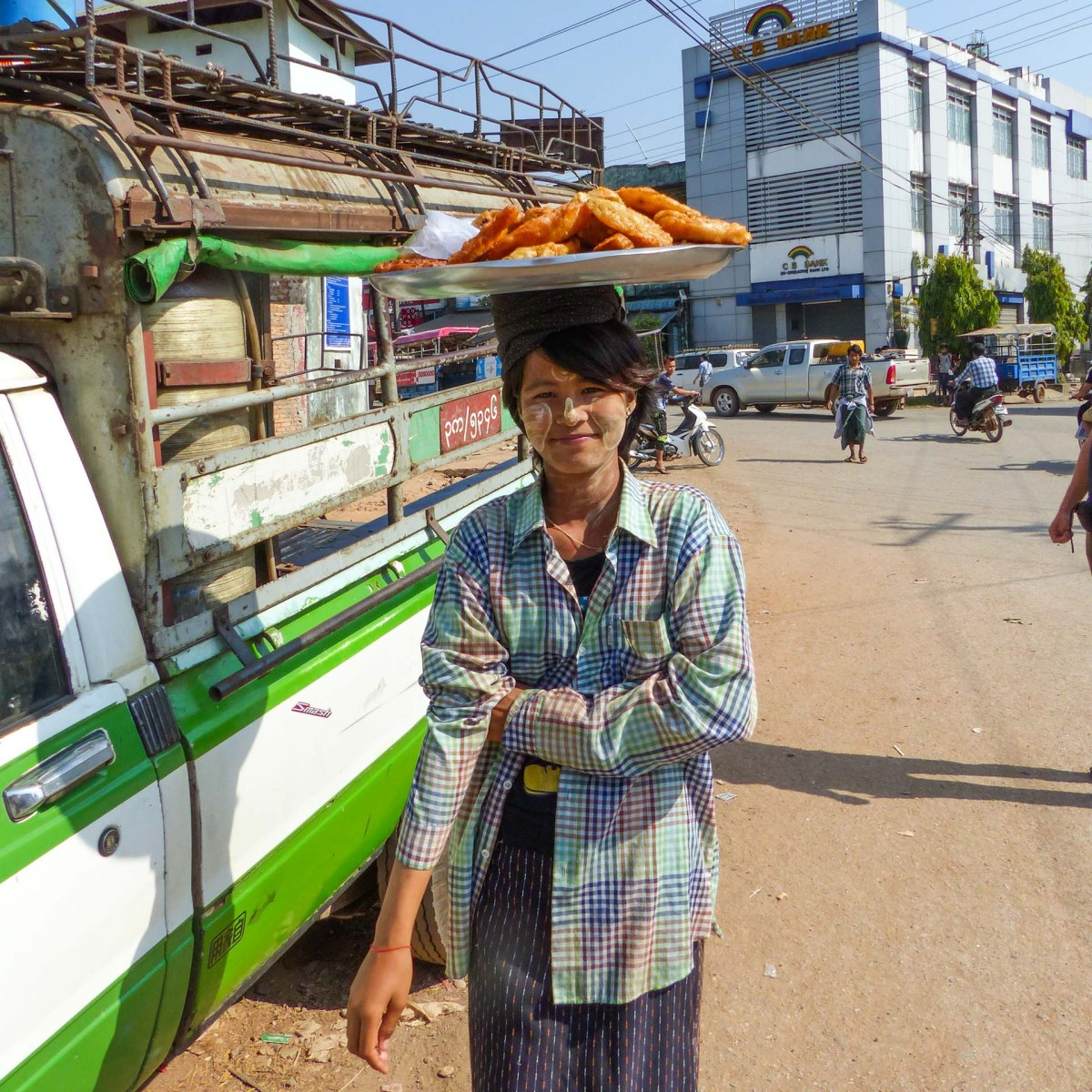 Woman with Thannaka in her face carries fried tofu on a large plate on her head in Hpa-An