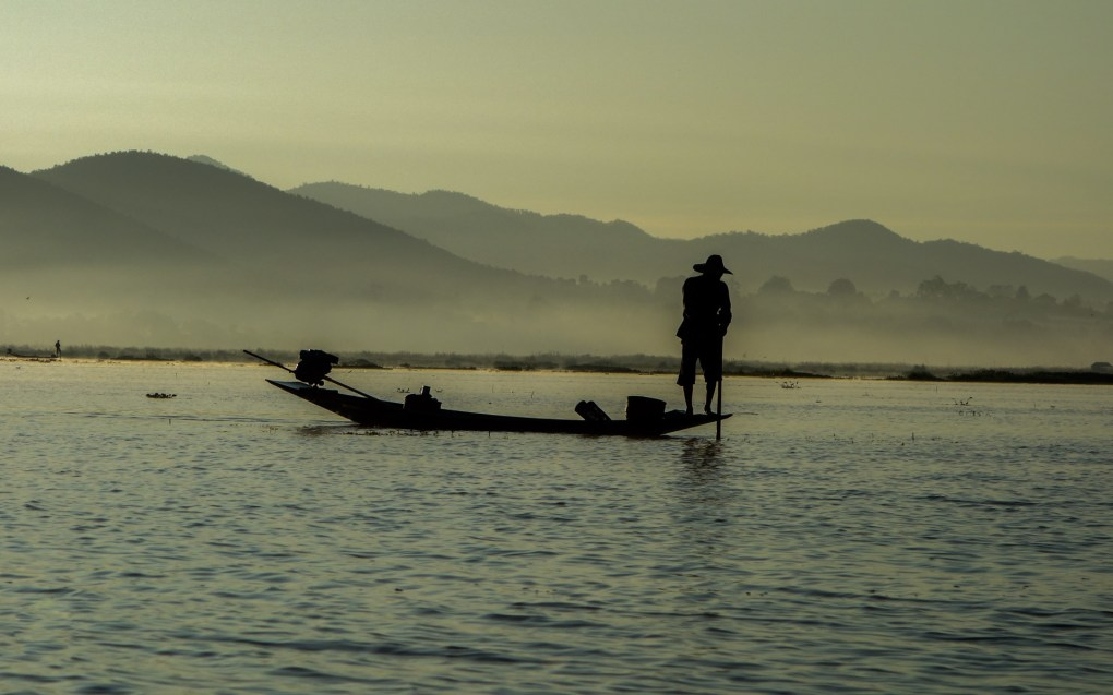 Leg-rowing Intha fisherman before sunrise on Inle Lake
