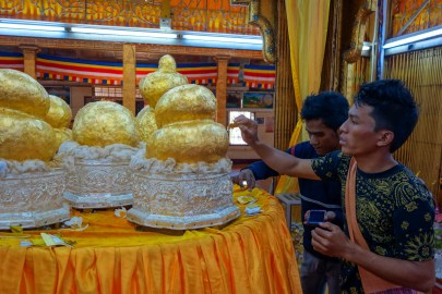 Men put gold leaves onto a relic in the Phaung Daw Oo Pagoda