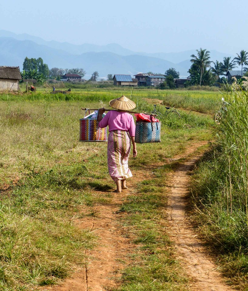 Burmese woman carrying goods in shoulder baskets along gravel road at Inle Lake
