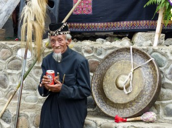 Tana Toraja Funeral Ceremony - happy parade master with gong and beer Christian Jansen & Maria Düerkop