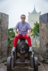 Rick sitting on a cannon in Macau taken just before our cruise to asia