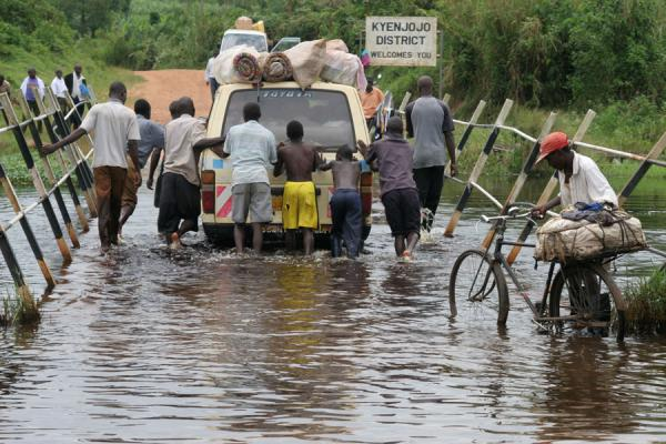 Image of Helping each other out: getting a car across a flooded bridge, Uganda people, Uganda