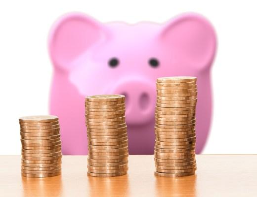 TravelAfter5_Dumb Travel Money Saving_Pink Piggy Bank looking at stacks of coins