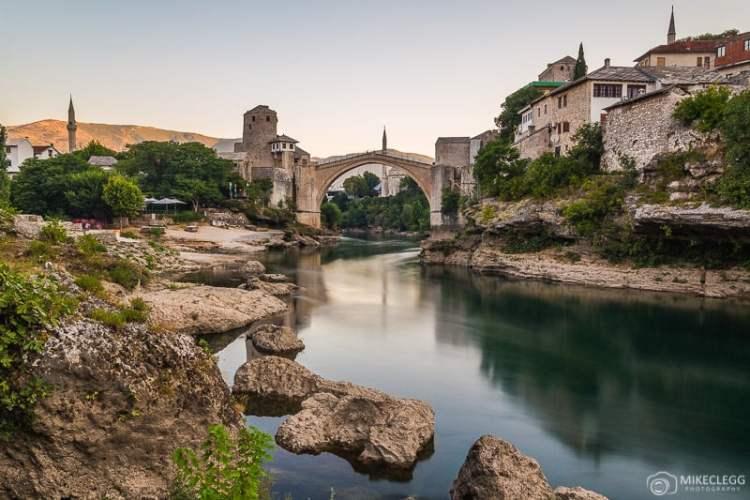 Mostar ao longo do rio Neretva com rochas em primeiro plano