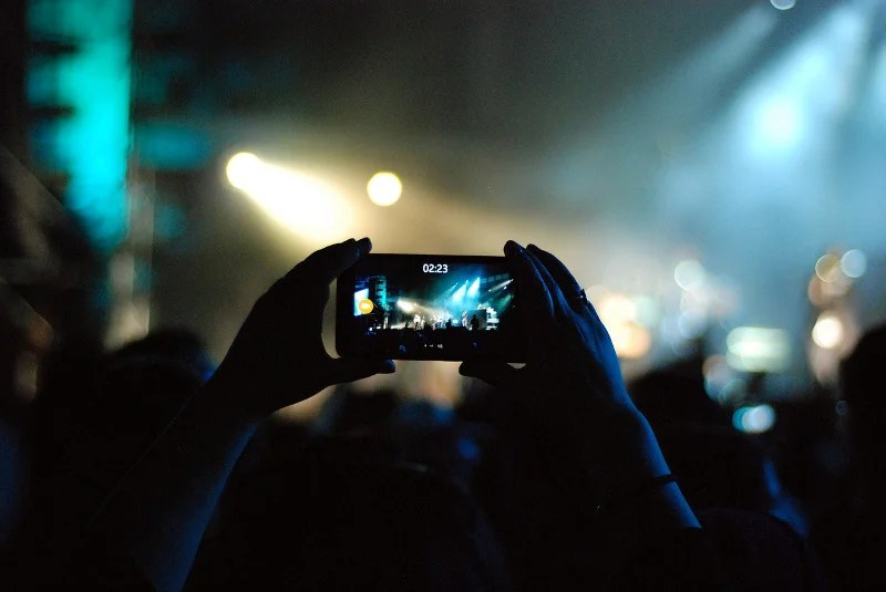 Uma pessoa gravando em um telefone em um festival - CC0 (Pixabay)