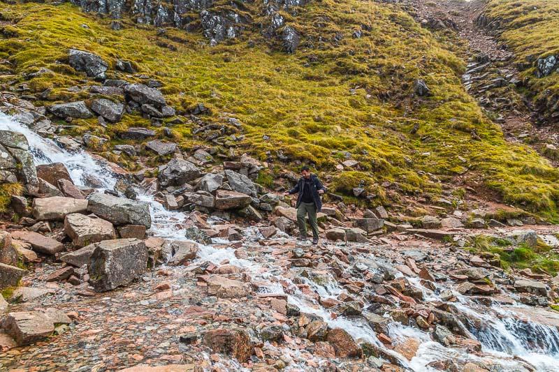 Caminhando sobre o riacho na trilha da montanha Ben Nevis