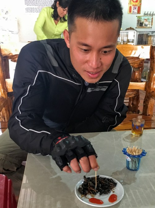 Our guide showing us how to eat the fried crickets Da Lat