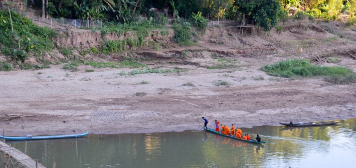 Monks crossing the Nam Khan River in Luang Prabang, Laos