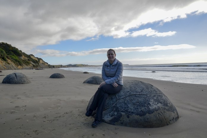 Sarah on a Moeraki Boulder in New Zealand