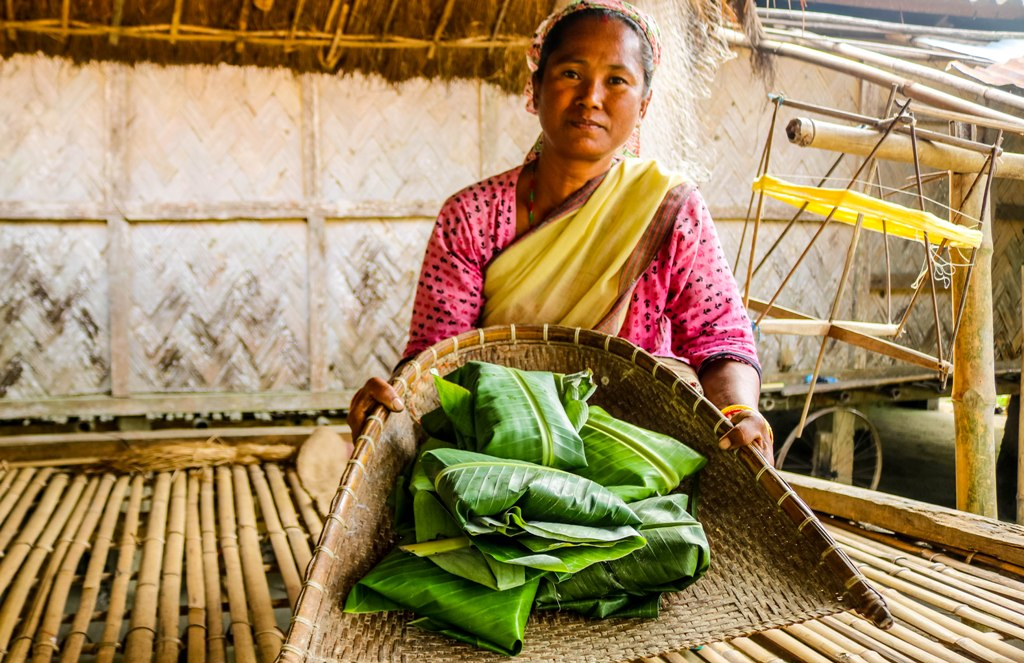 Mishing woman with traditional meal serving in an authentic way