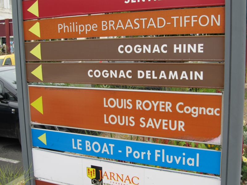 Street signs pointing the way to various cognac distilleries in Jarnac near Cognac in France
