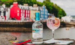 A bottle of Tobermory Hebridean Gin with a gin and tonic cocktail