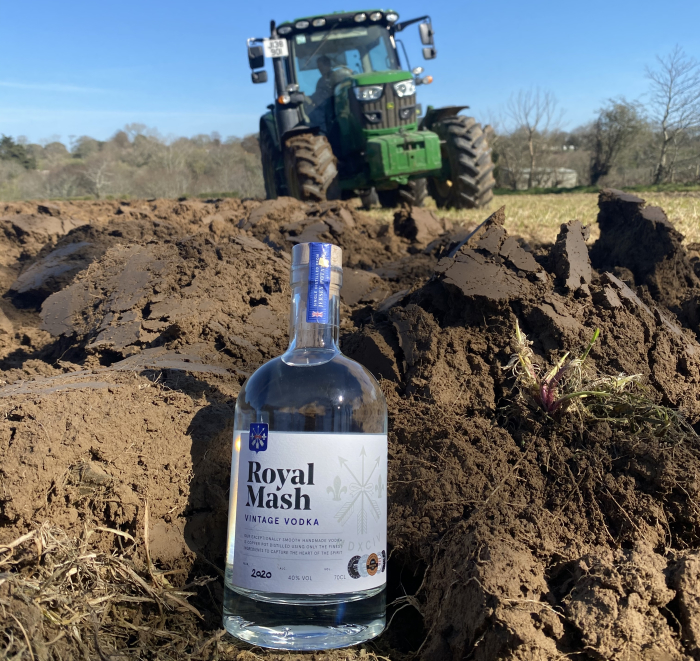 A bottle of Royal Mash Vintage Vodka in a field with a tractor behind it