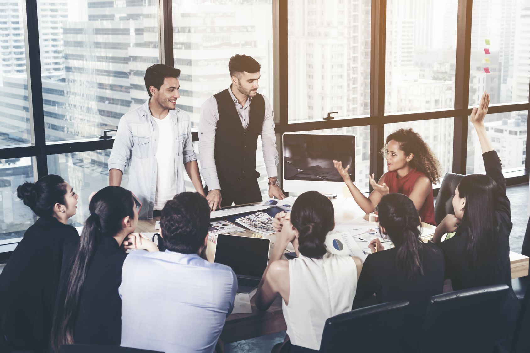 Successful Team Leader And Business Owner Leading Informal In House Business Meeting Business People Working On Laptops In Foreground And Glass Reflections Business And Entrepreneurship Concept Traveldoo