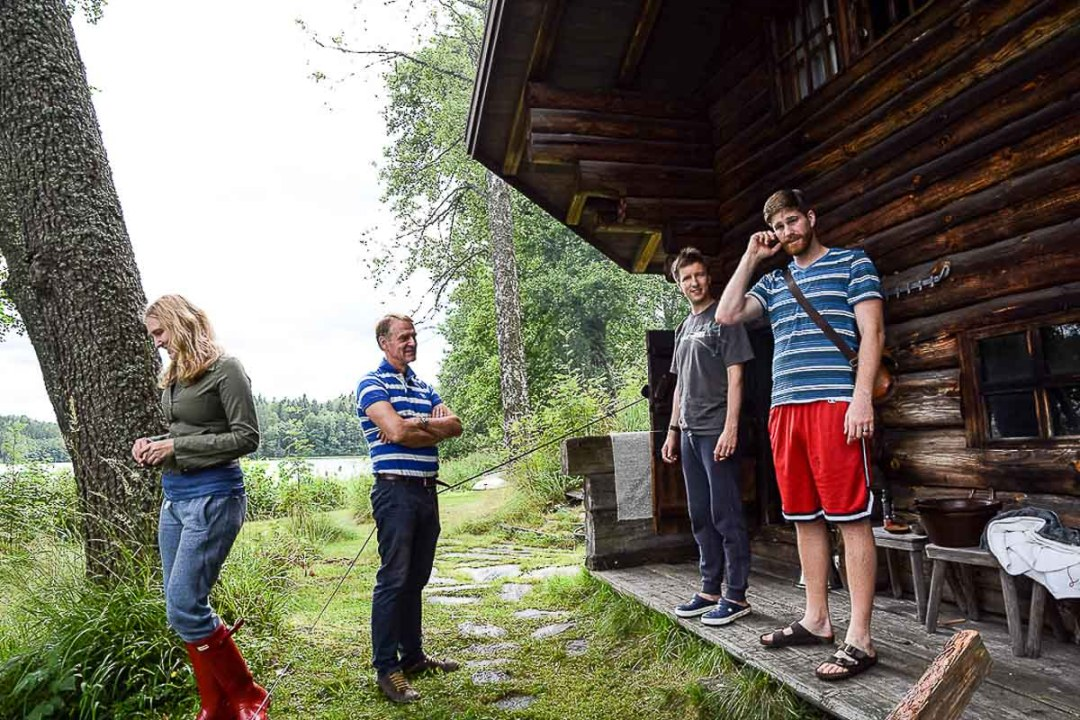 Four people standing outside of a smoke sauna in Finland.