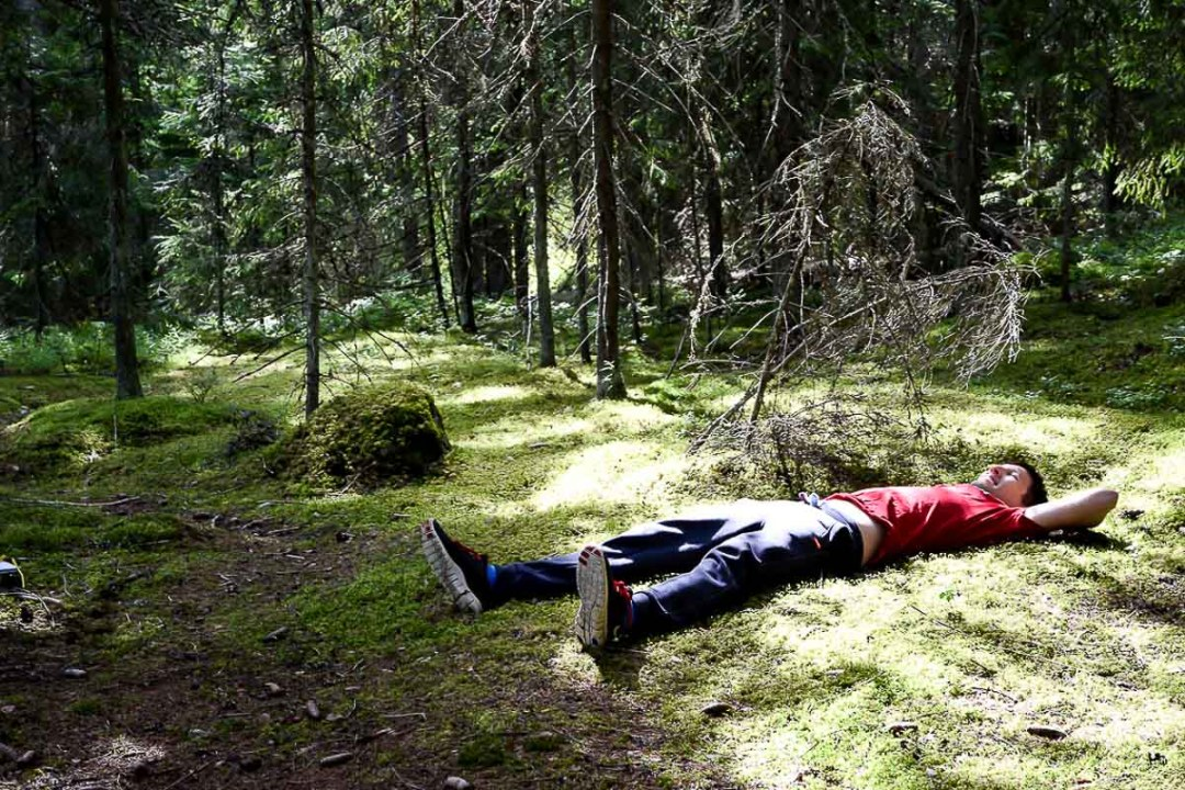 man laying down on the moss in a Finnish forest