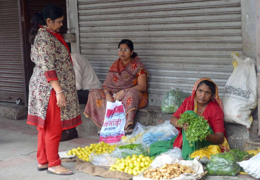 3 ladies sitting on the foot path selling vegetables
