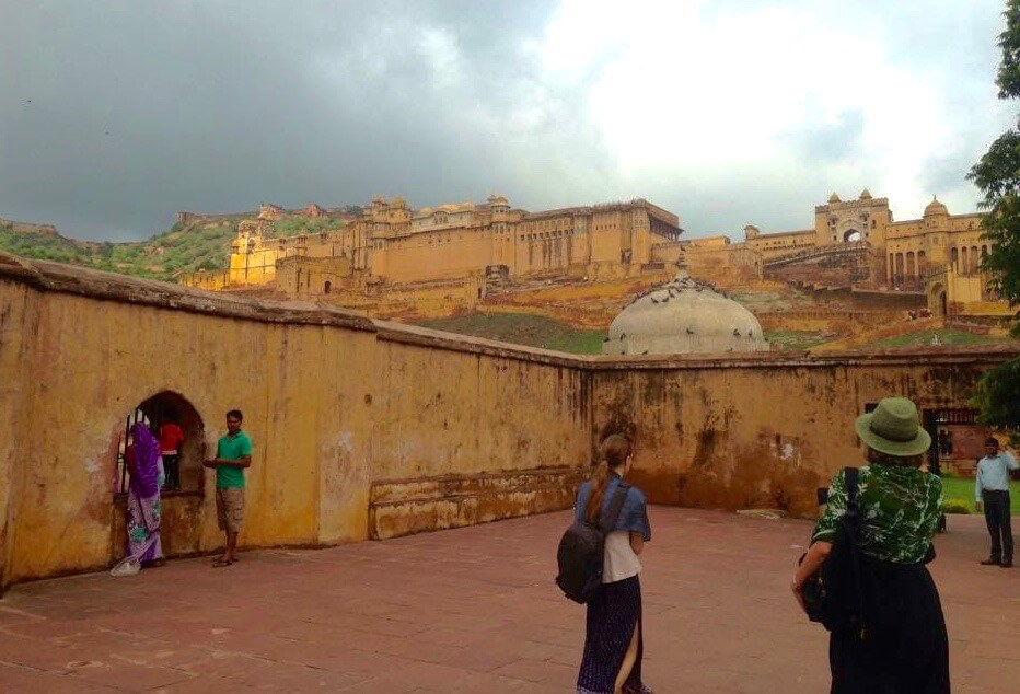 2 tourists walking towards a huge hill covered in the Amber Fort