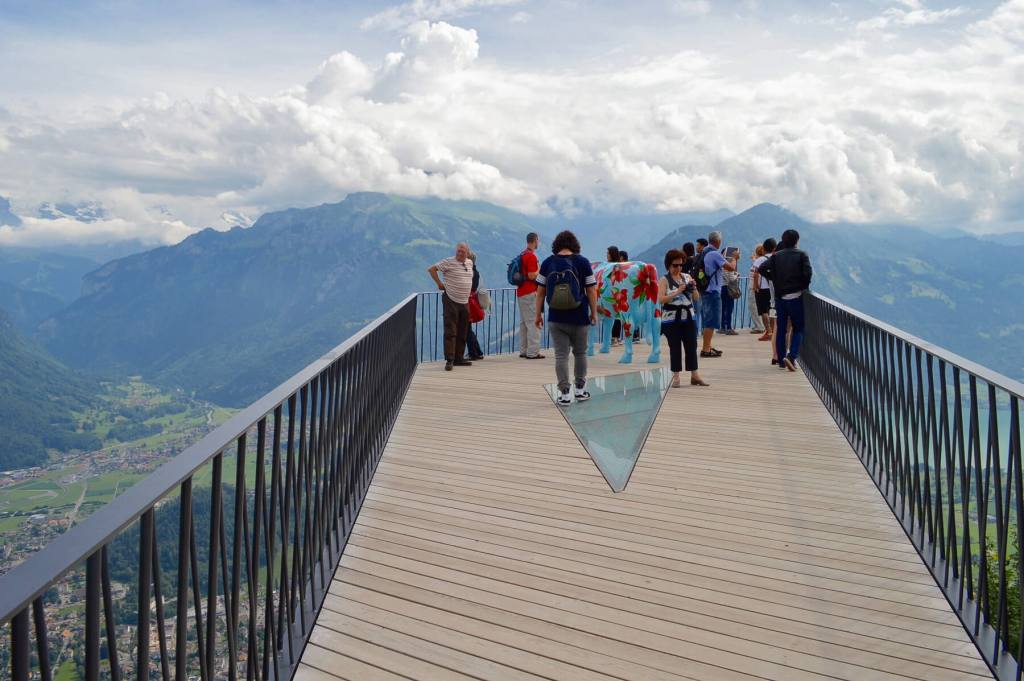 A group of tourists standing on the floating lookout platform, overlooking Interlaken