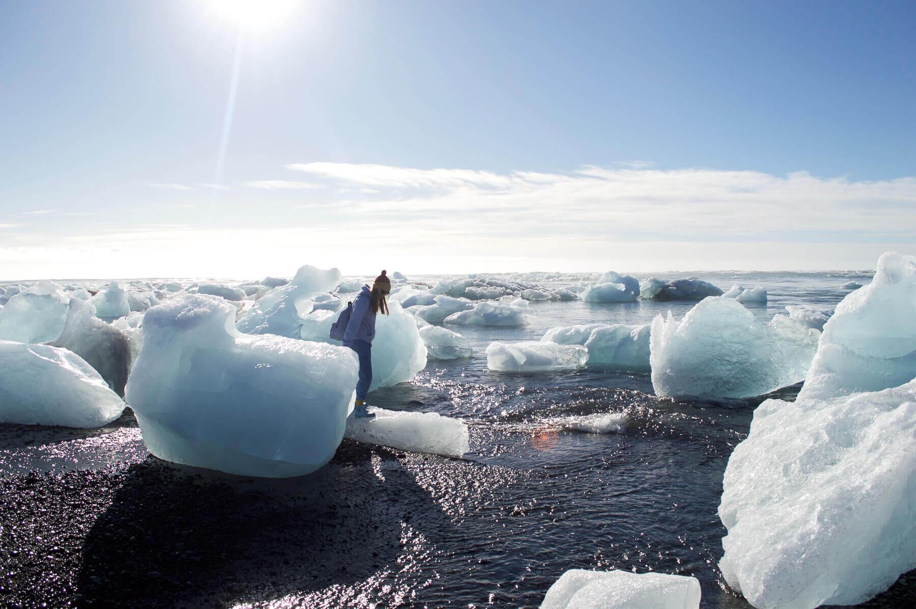 Girl standing on icebergs on diamond beach iceland