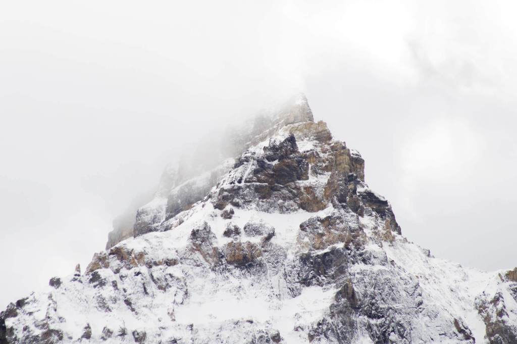 Close up of a pointed mountain peak surrounded by fog