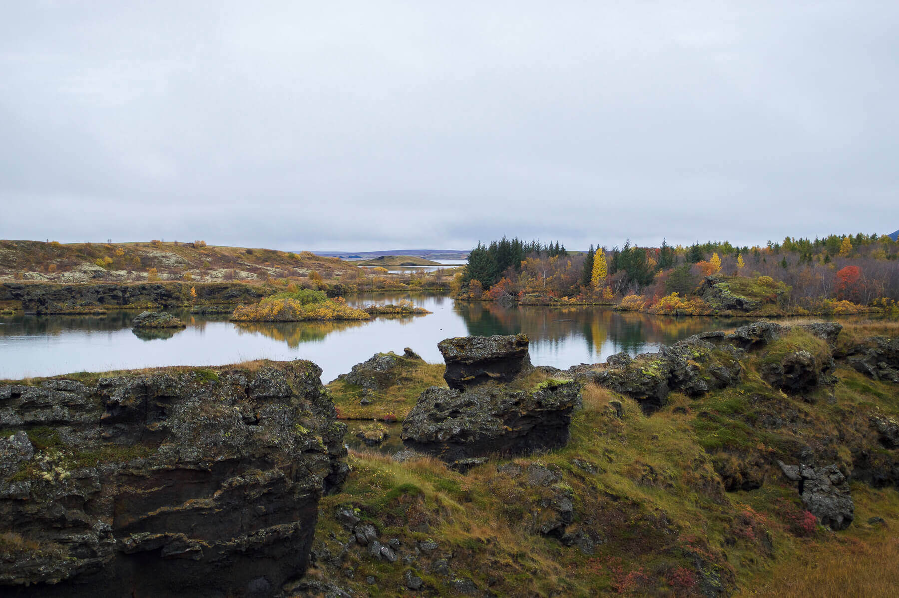 A lake surrounded by rocky land an autumnal trees