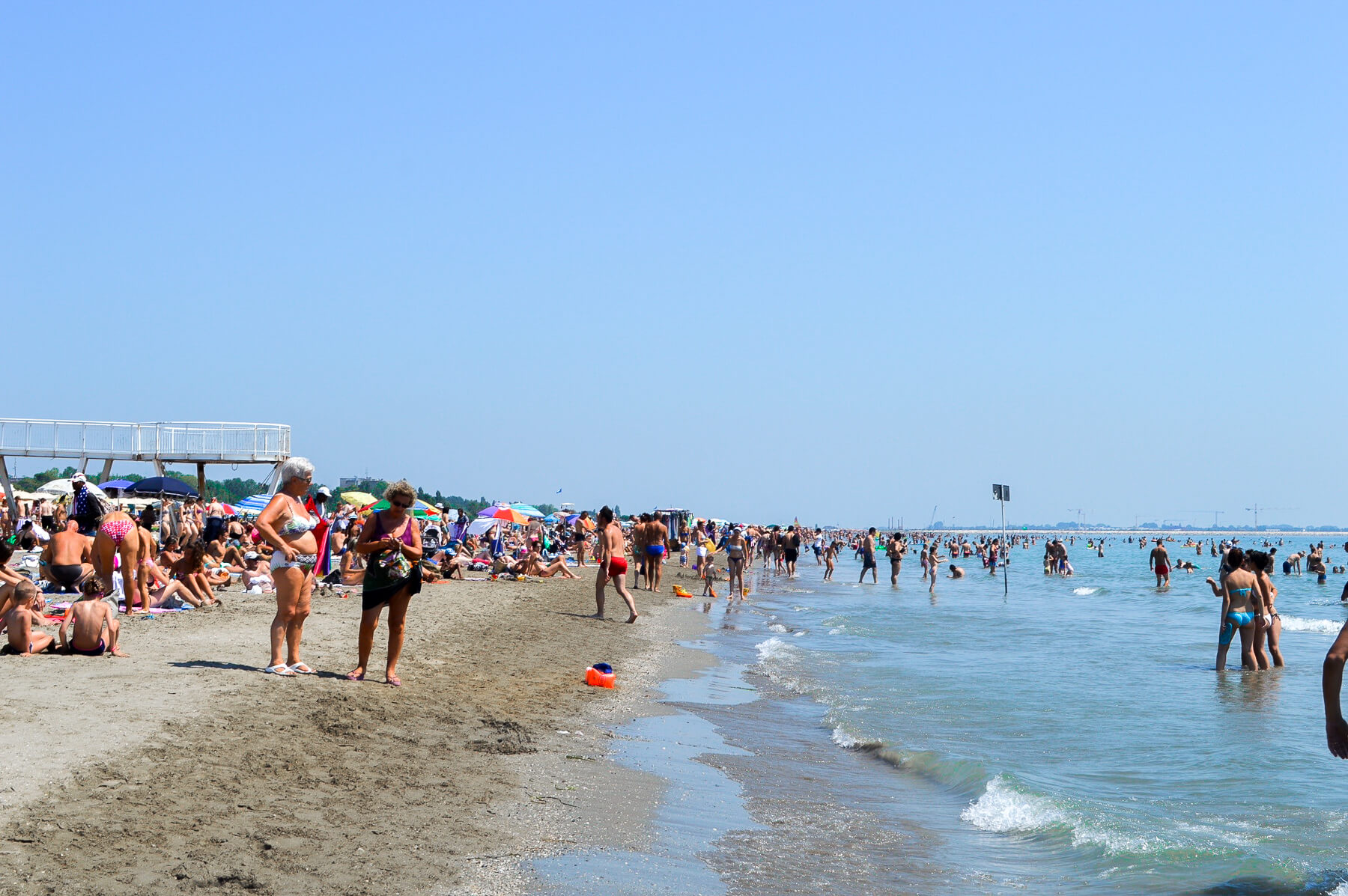 white sand beach and ocean with thousands of people