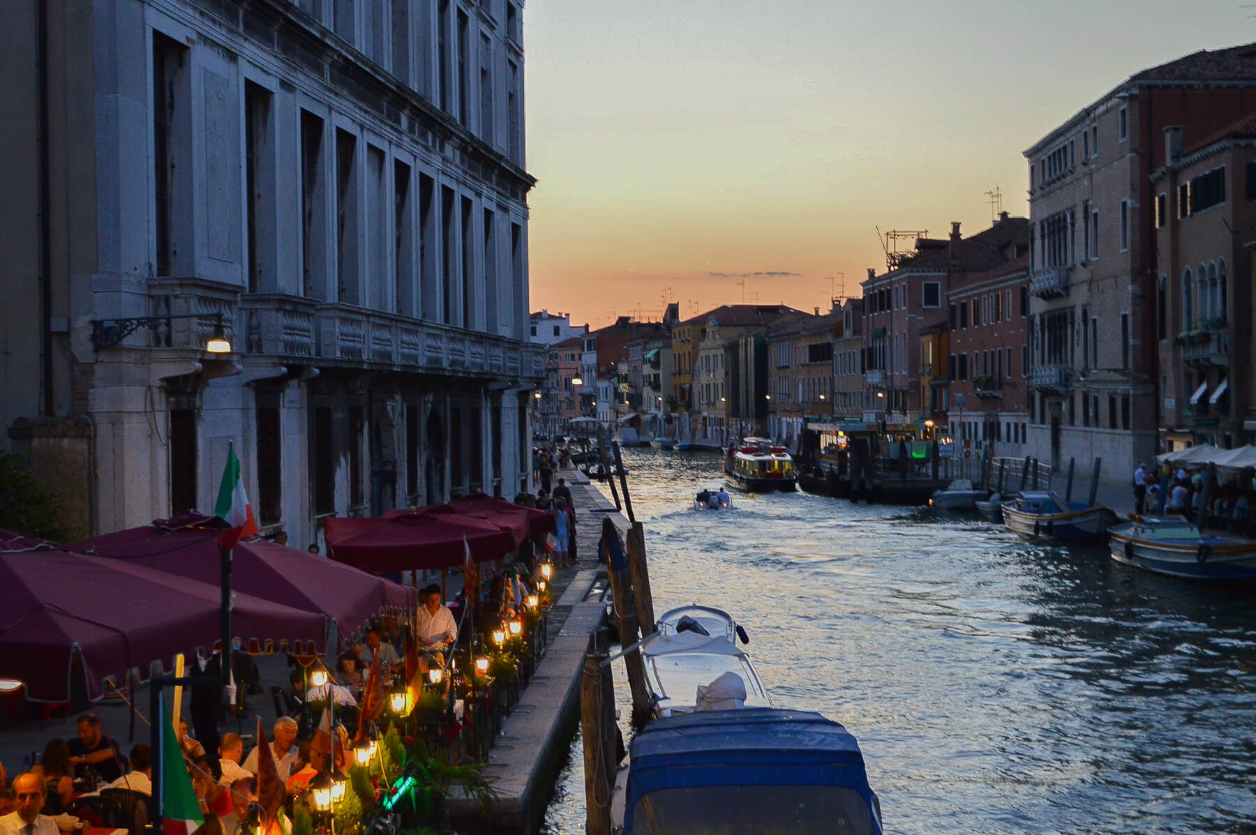 sunset behind canal with boats and restaurants