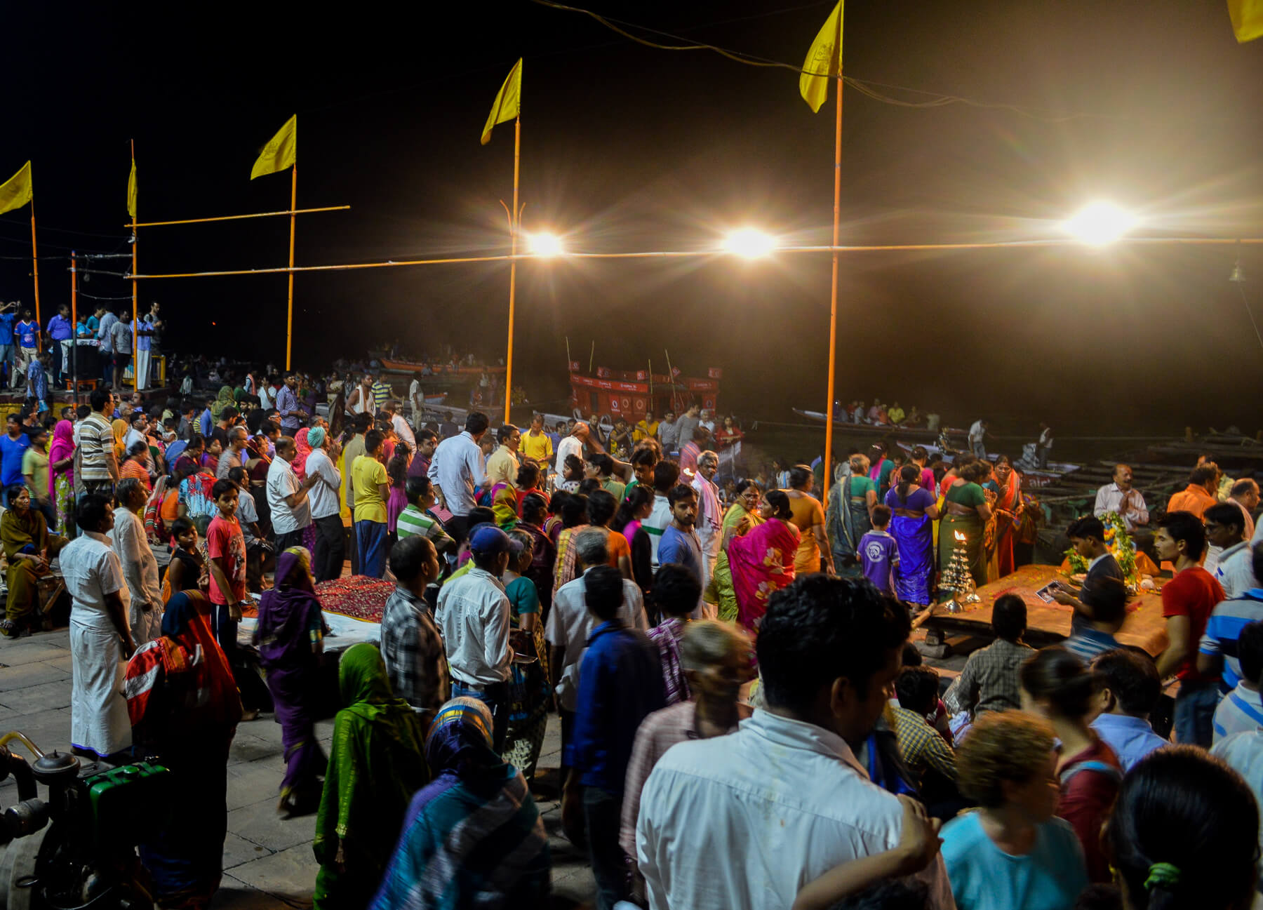 Mass crowds along the river in India after dark