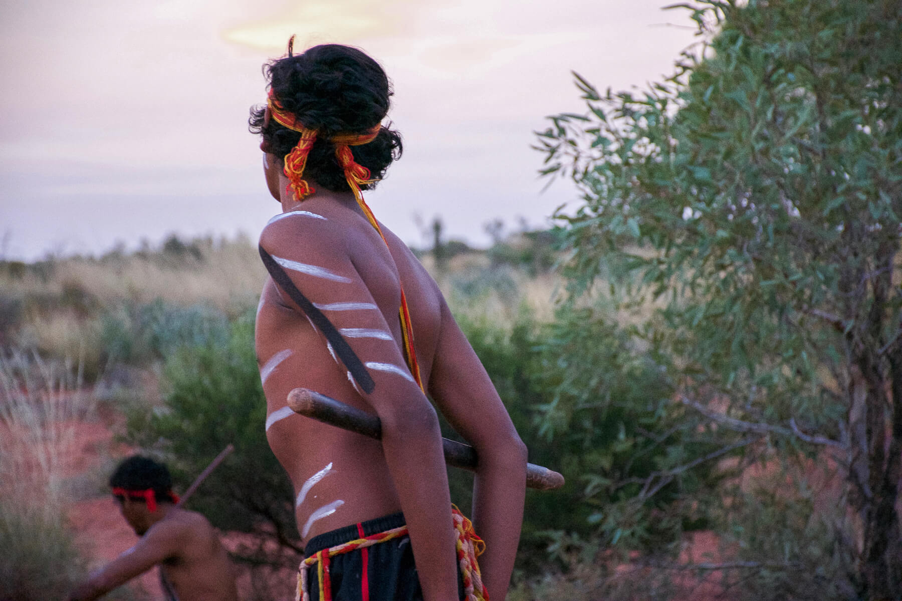 2 Indigenous dancers with body paint in the shrubbery