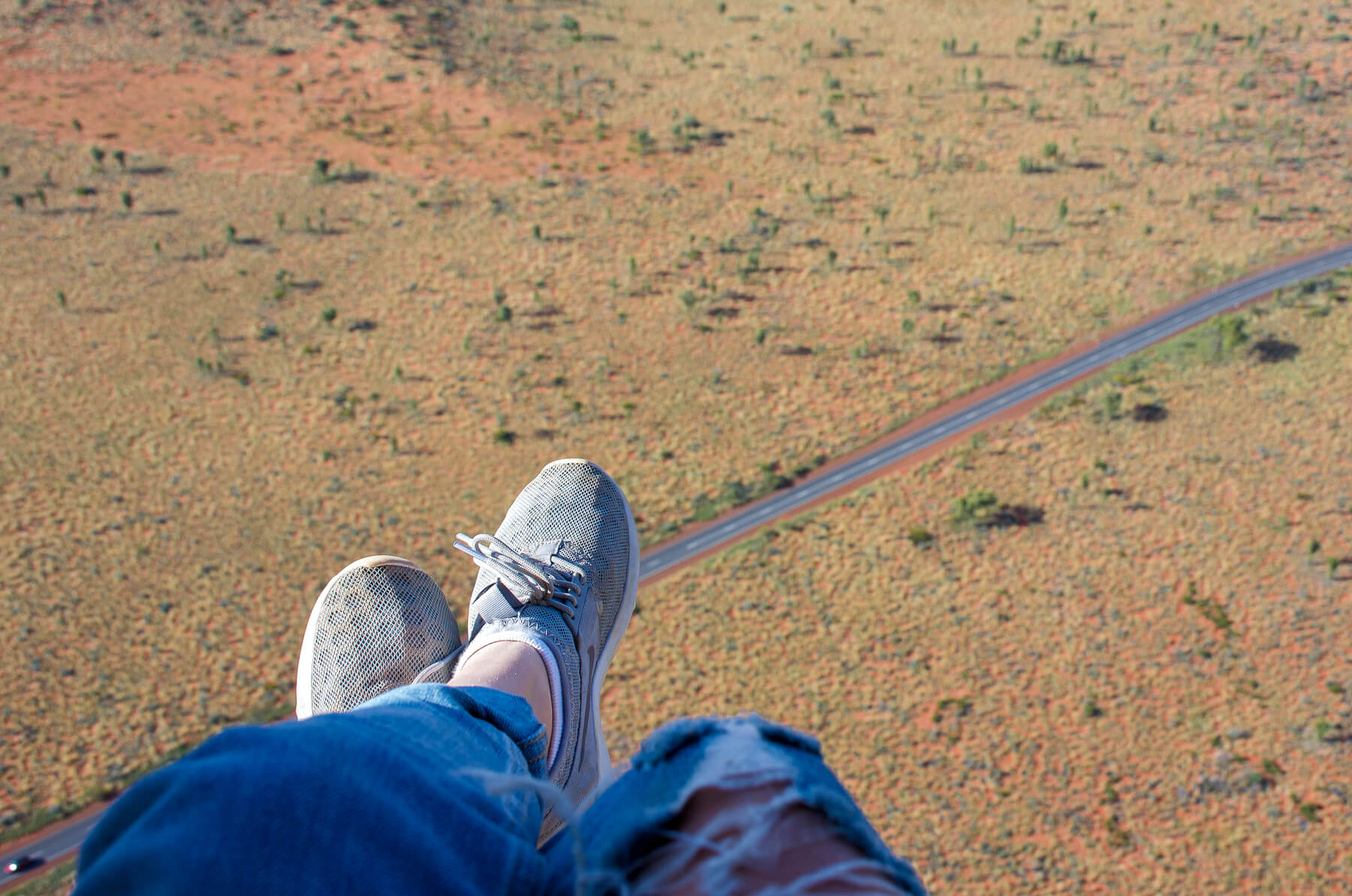 Feet hanging from a helicopter high above the Australian Outback