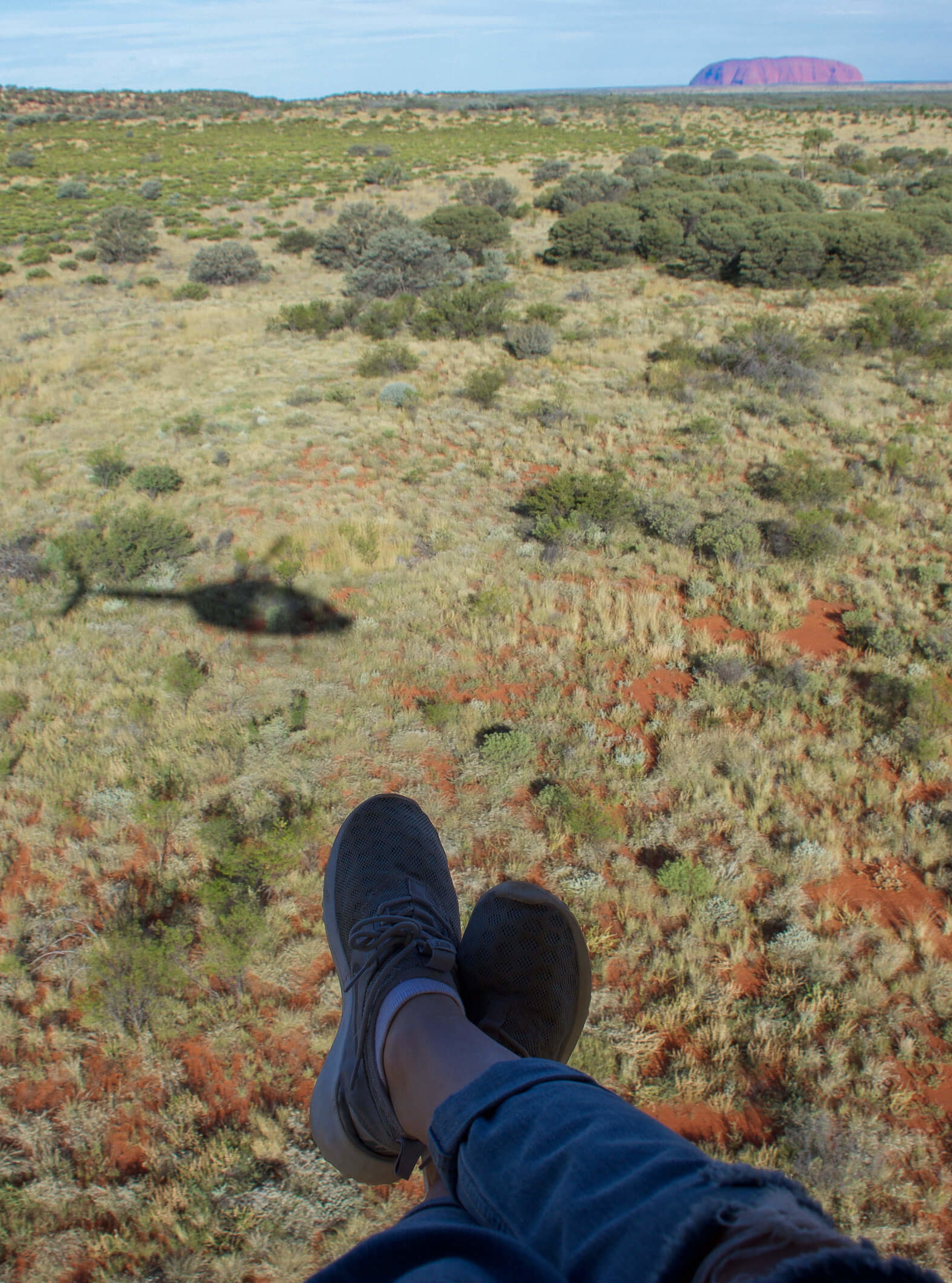 Feet hanging in the air with Helicopter shadow and Uluru in the background