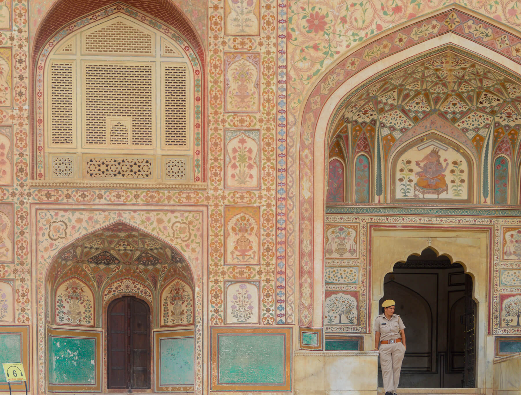 Lady standing infront of amazing palace front in India