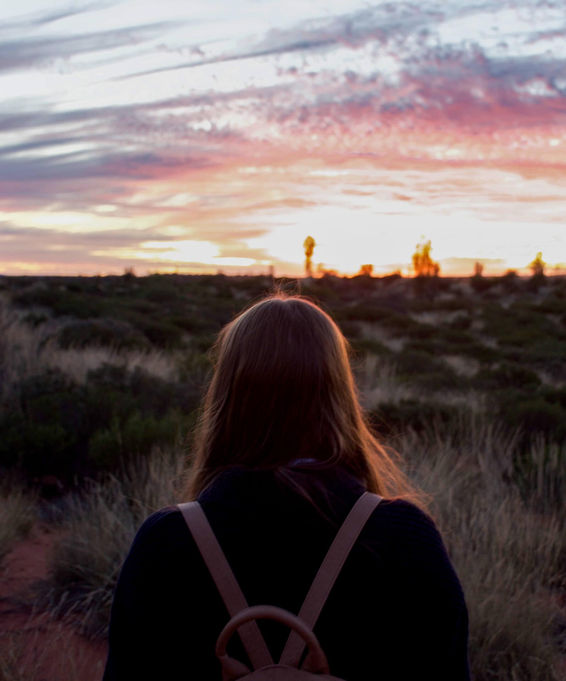 Girl looking towards vivid sunset