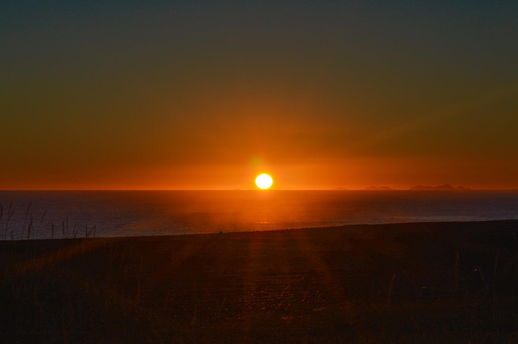 Orange sun shining over the horizon