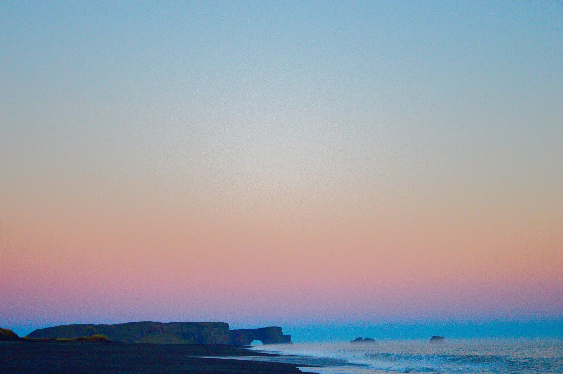 Sunset over Iceland's black beach and Dyrholaey