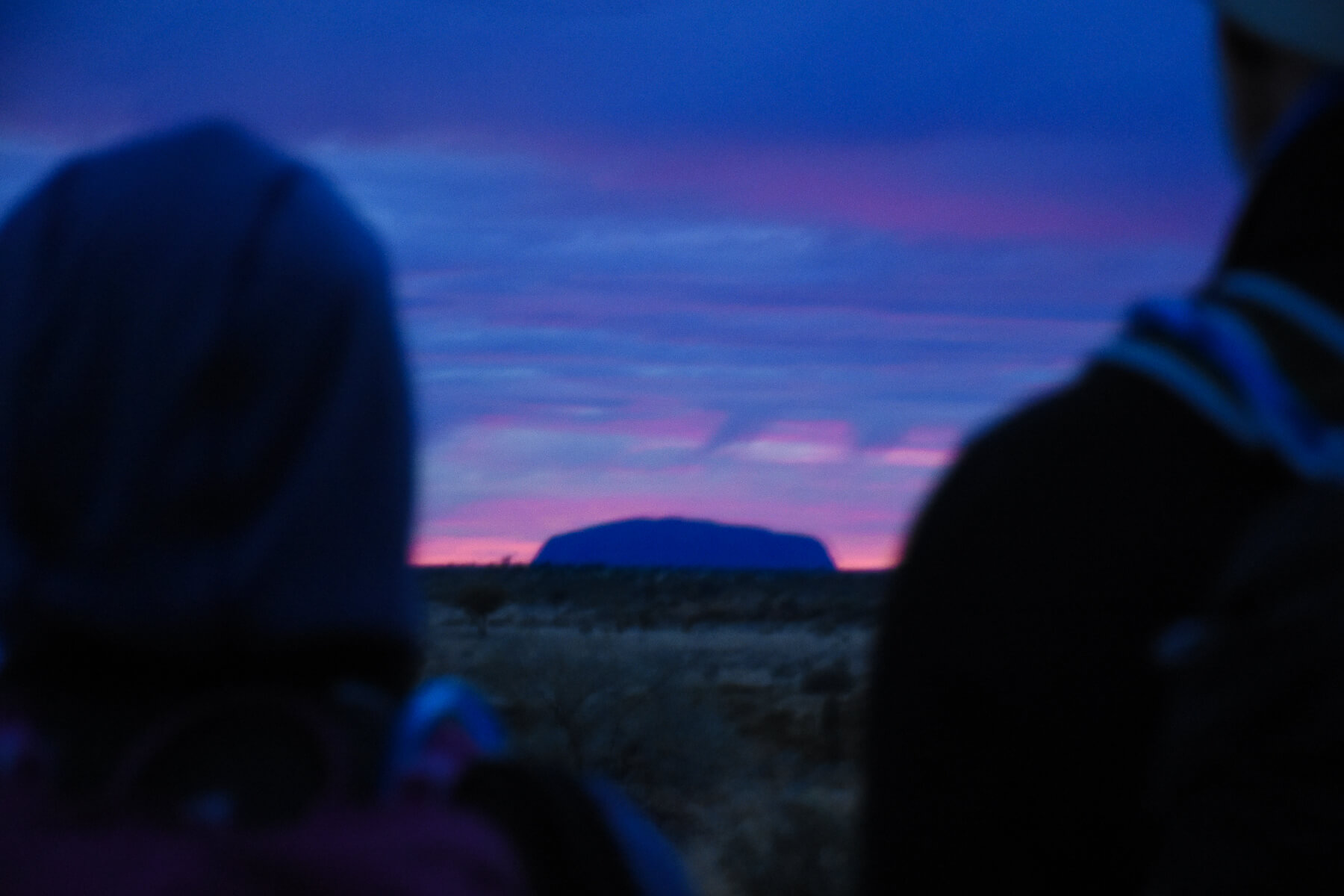 Bright Blue sunrise behind Uluru - camera pointing between 2 out of focus bodies