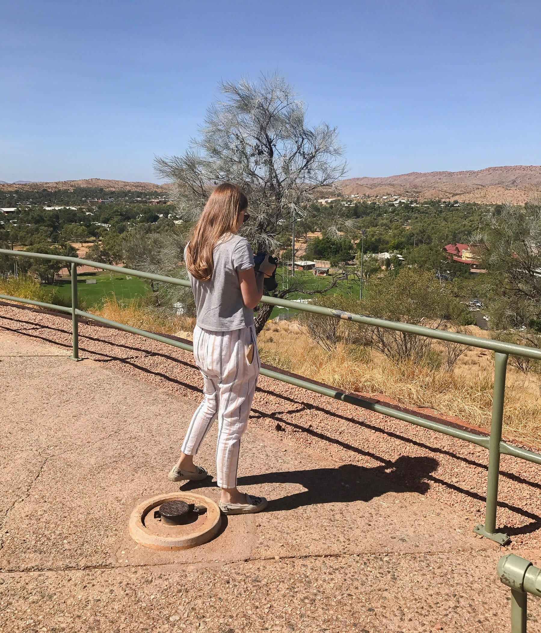 Girl looking at camera onto of Anzac hill in Alice Springs