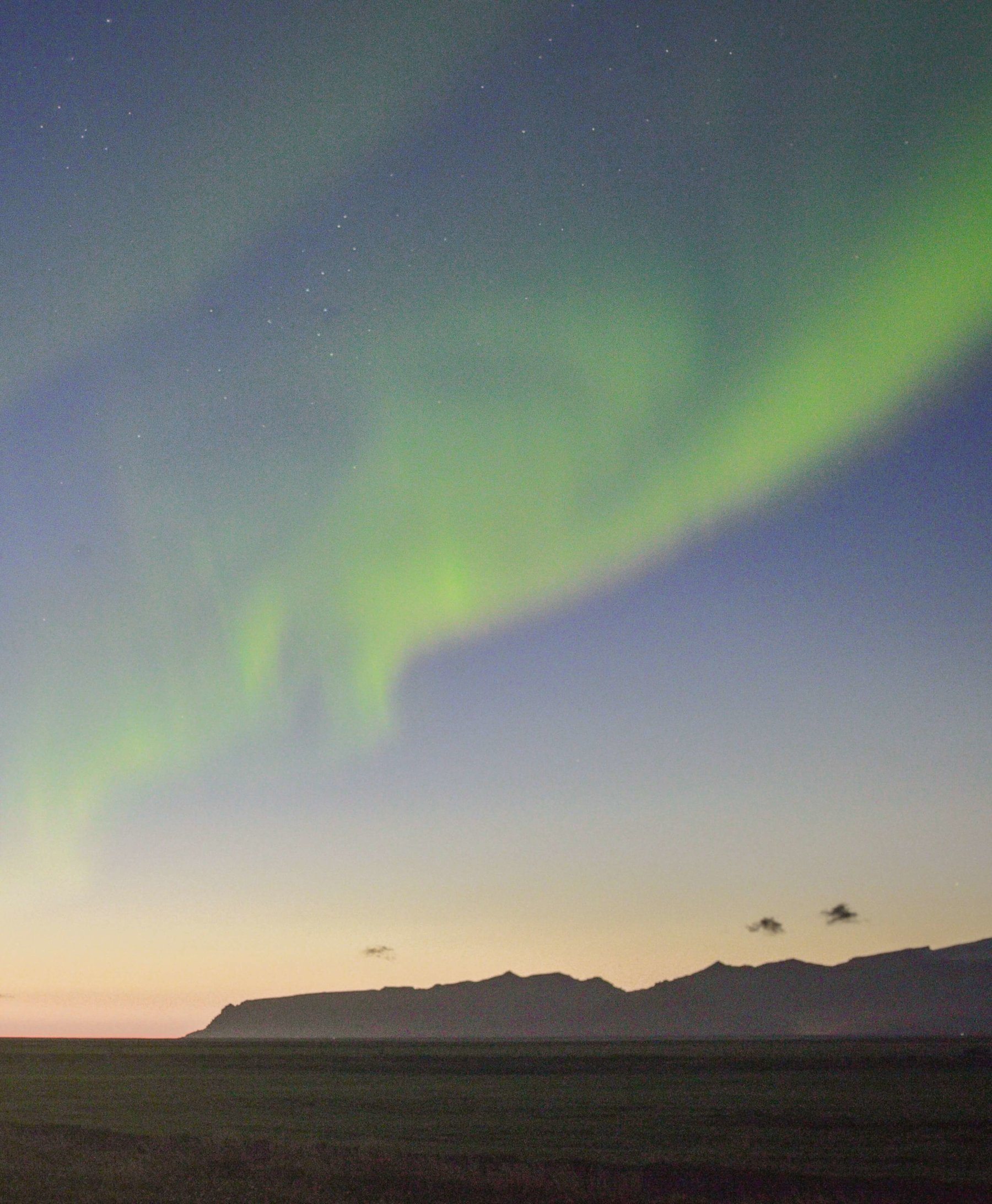 The Northern Lights swirling through the sky above distant mountains and a golden glow