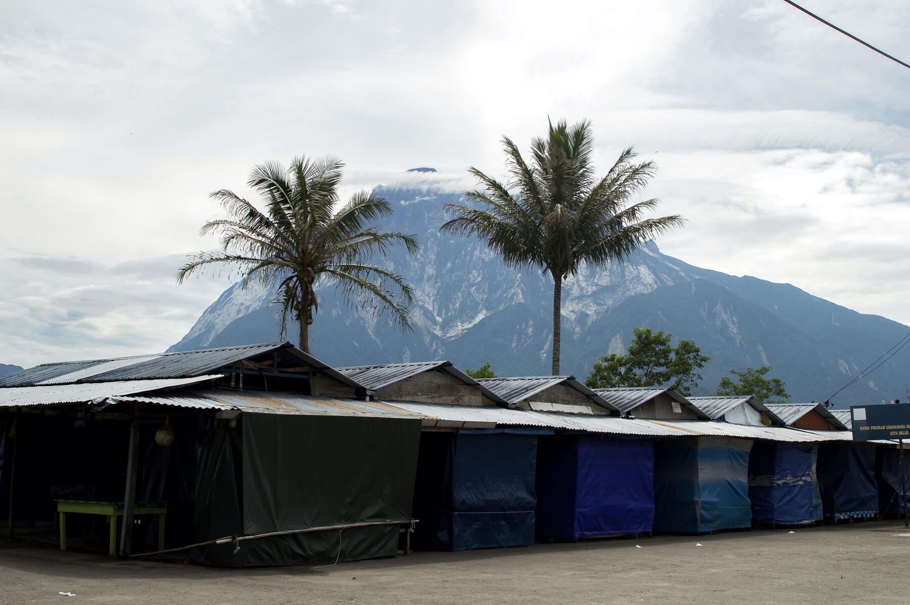 Stalls and palm trees in front of Mount Kinabalu