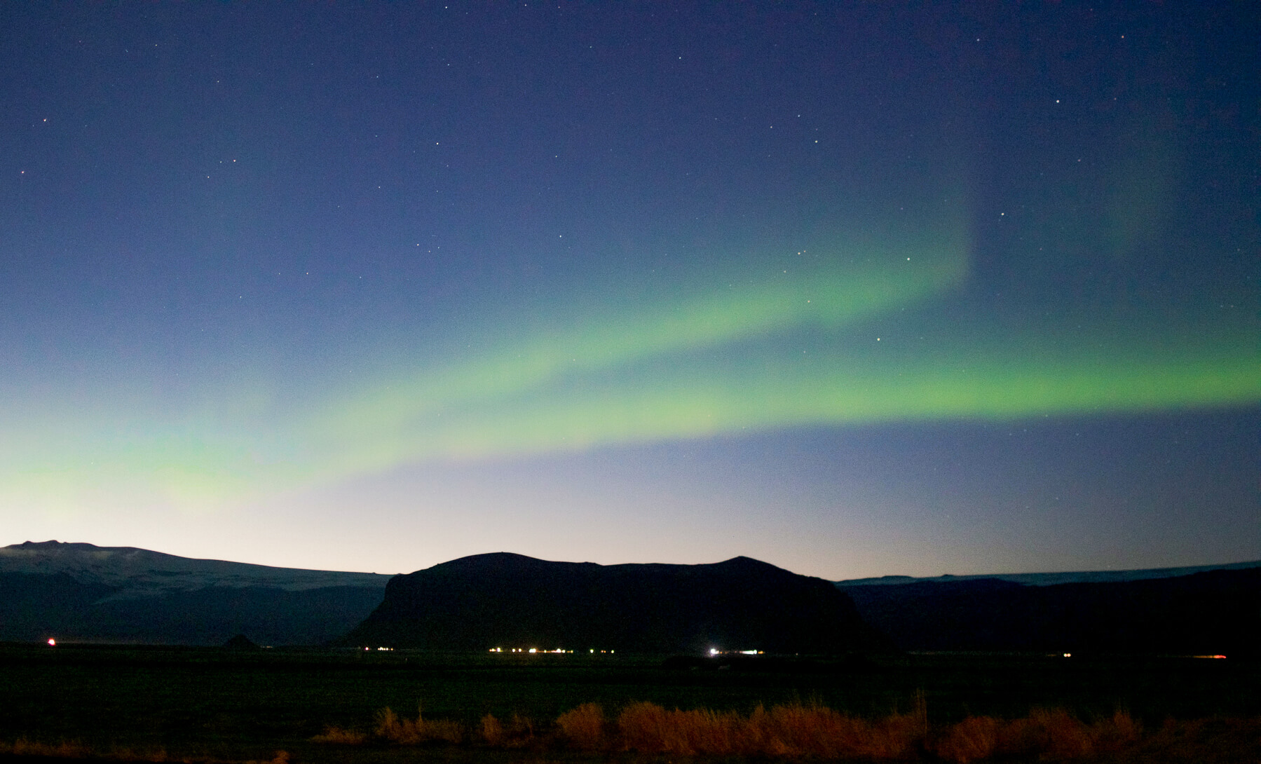 Thin stream of Northern Lights running across the sky above mountains and a distant town