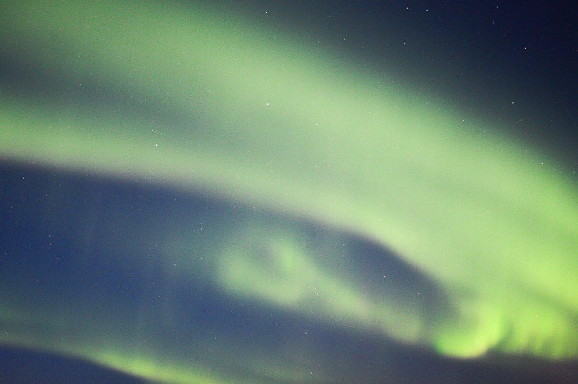 Green Aurora swirling through the Midnight Sky