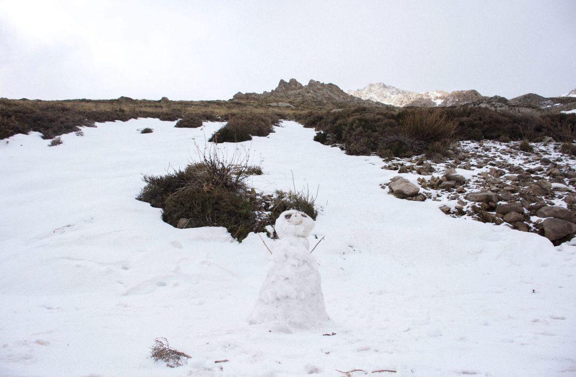 Snow man at the bottom of a mountain - looking up at the peak