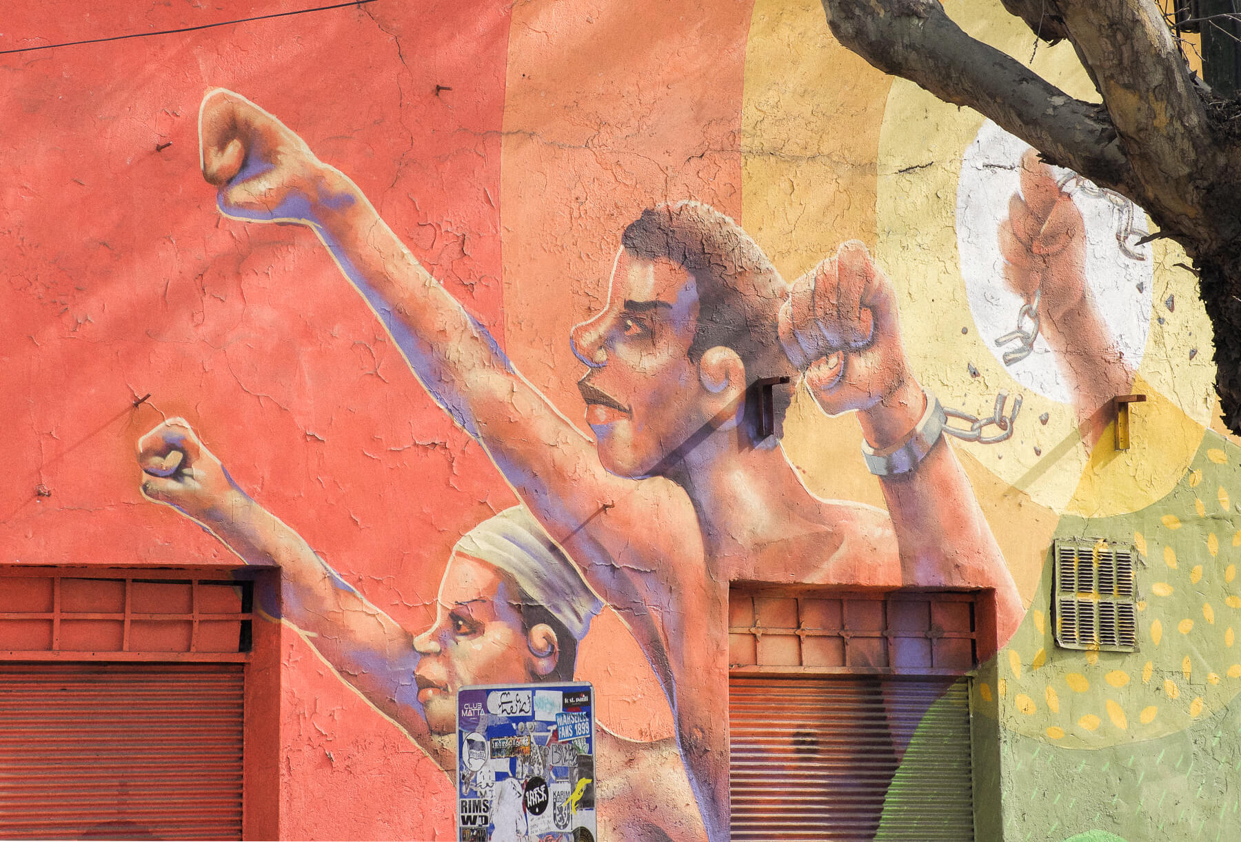 Rainbow artwork on the side of a building of 4 dark skinned fists breaking free of chains