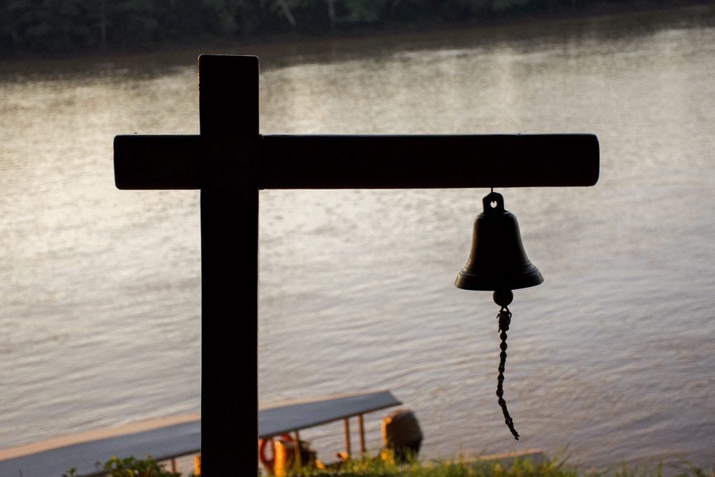 An old bell with the river and the roof of a boat behind it
