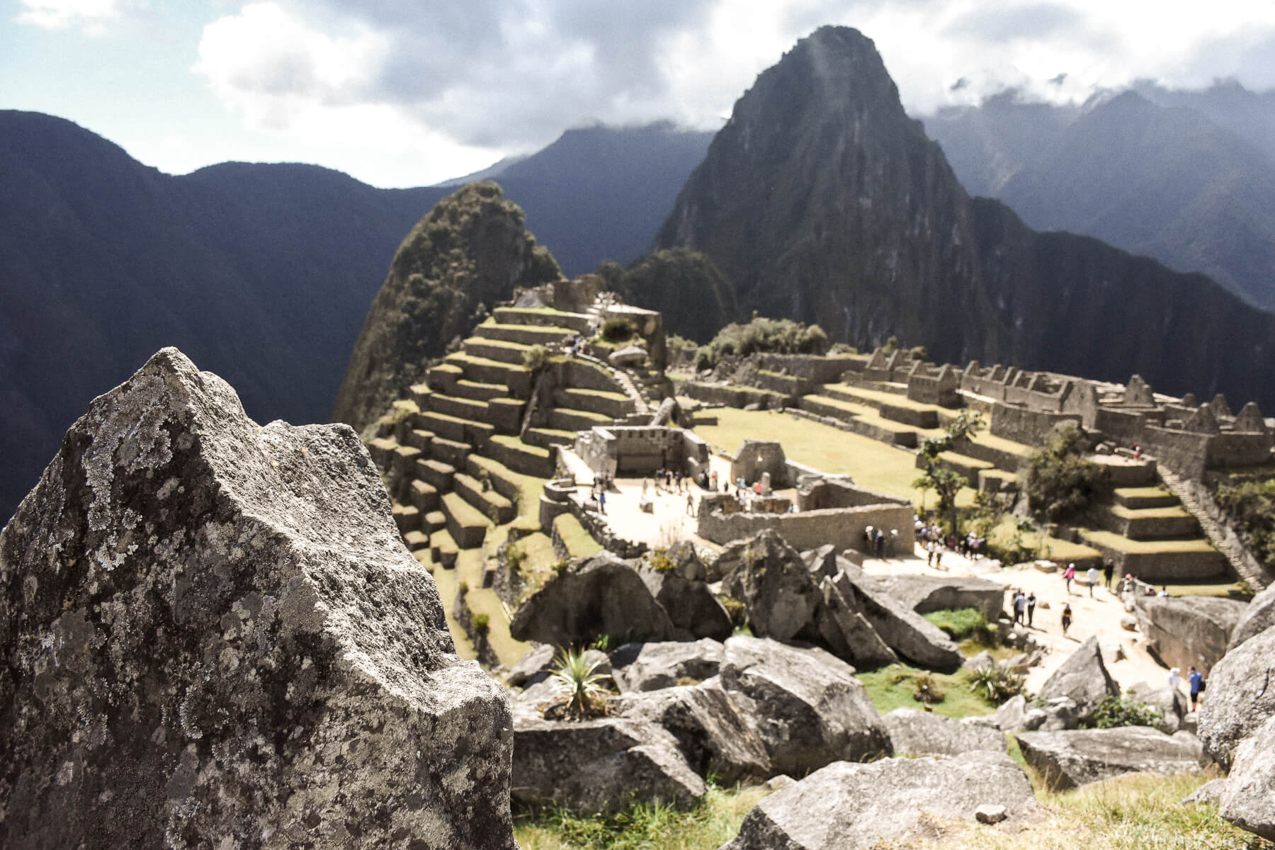 Camera focused on a huge stone with Machu Picchu blurred in the background