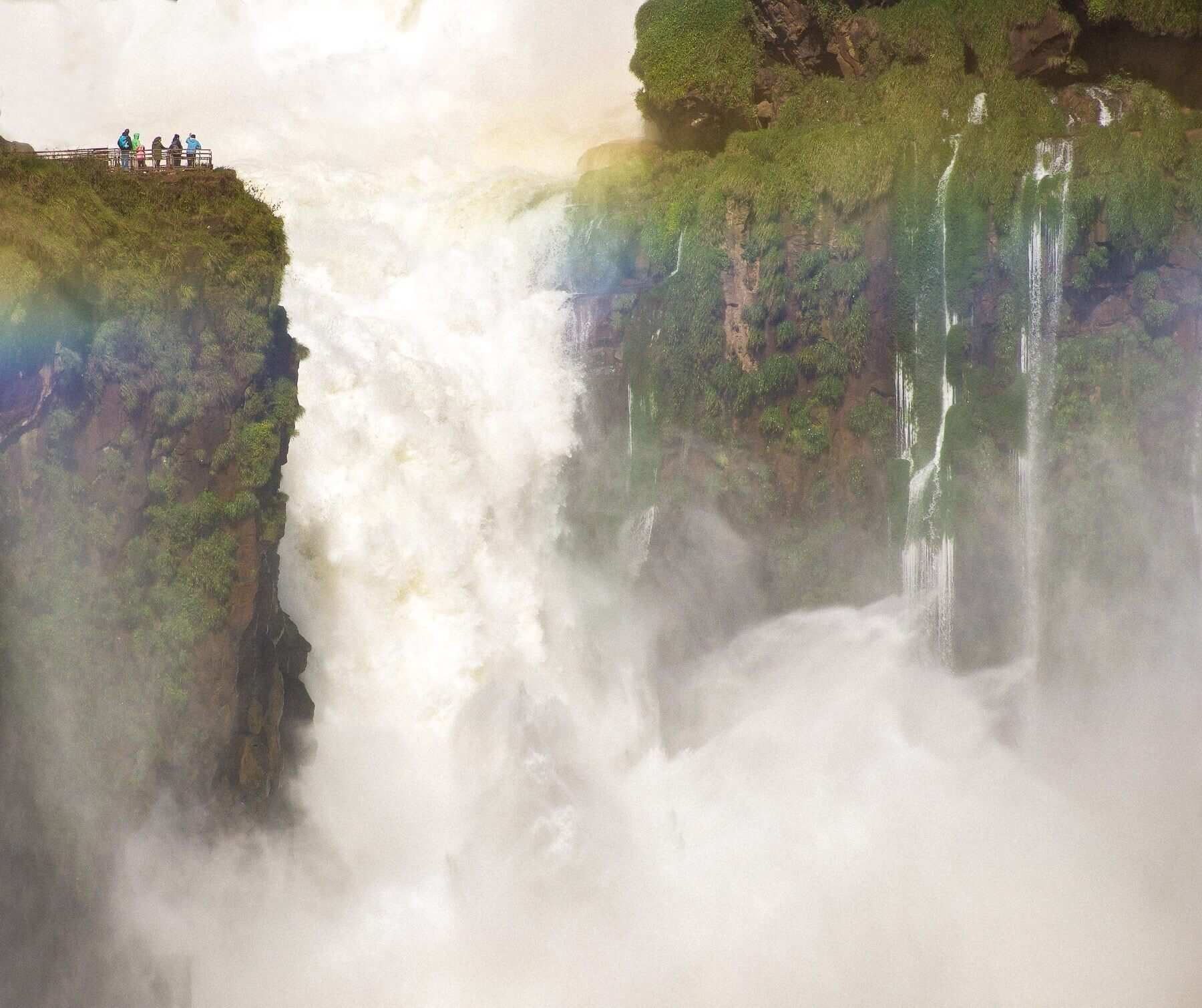 A ginormous waterfall with people in the top left hand corner showing the size